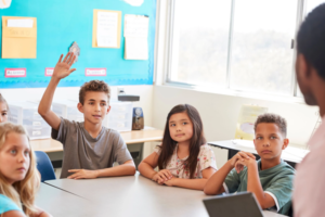 kids in a class, one is raising their hand to ask a question